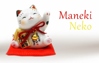 Escultura de maneki neko saludando sobre un cojín rojo