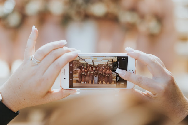 Close up of hands holding an iphone and taking a photo of a bride and her bridesmaids
