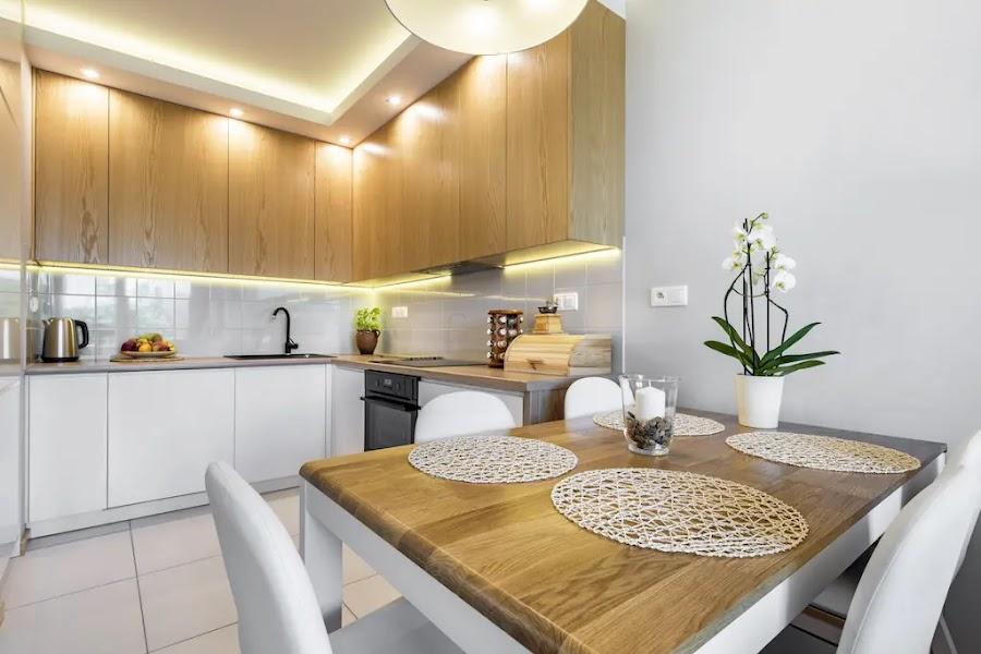 cocina moderna con mobiliario en blanco y madera, y luces de led