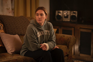 Kate Winslet wearing a hoodie and sitting on a sofa