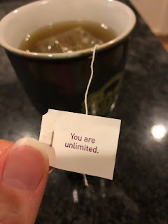 Brewing tea in my grey tea cup as I hold the tea-bag tag that says: You Are Unlimited