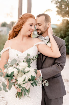 groom and bride with big green and white bouquet