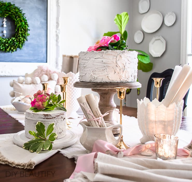 dining table styled with fake cakes and fresh flowers