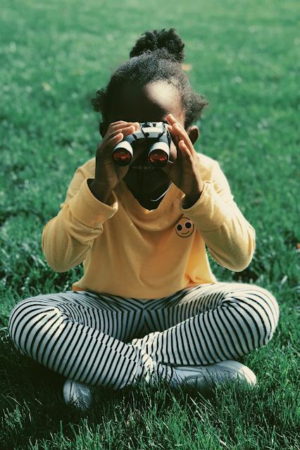 Girl sitting on grass with binoculars watching nature