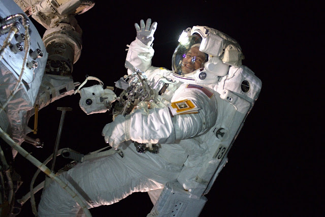 Drew Morgan floating in space attached to the ISS