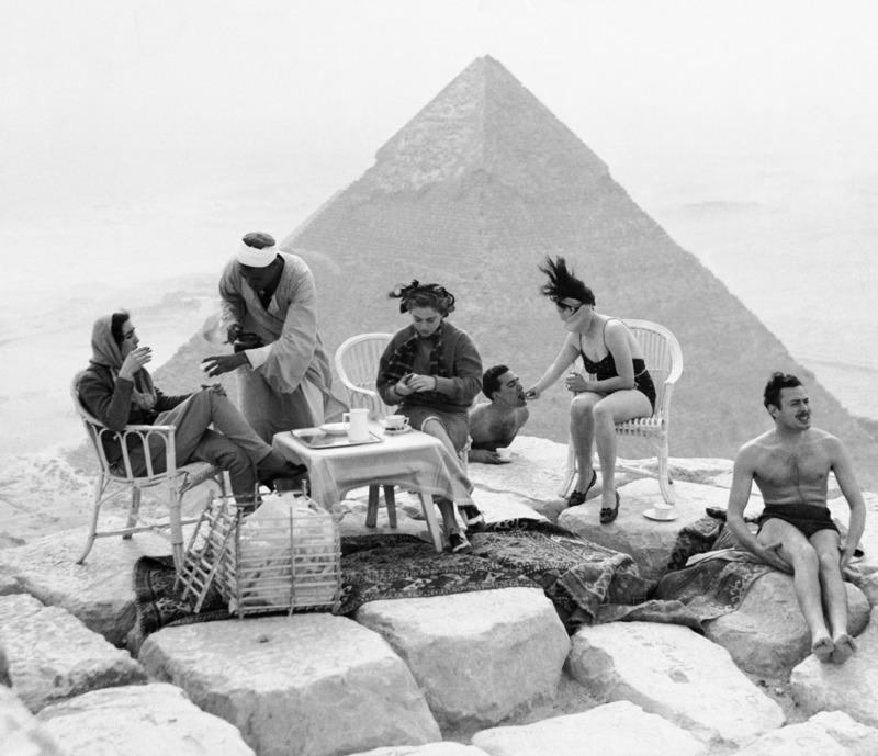 Turistas descansan sobre una de las pirámides de Giza en 1938