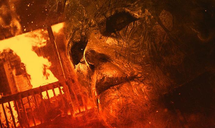 Imagem de capa: pôster do filme com a máscara de Michael Meyers, um rosto humano com dois buracos escuros no lugar dos olhos, completamente rachada e queimada de um lado e por trás uma casa ardendo em chamas.