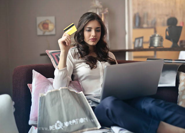 Brunette lady holding a credit card and doing her shopping online.