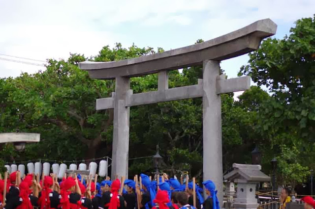 Costumed in traditional uniforms, prayer at Shinto Shrine, Torii gate