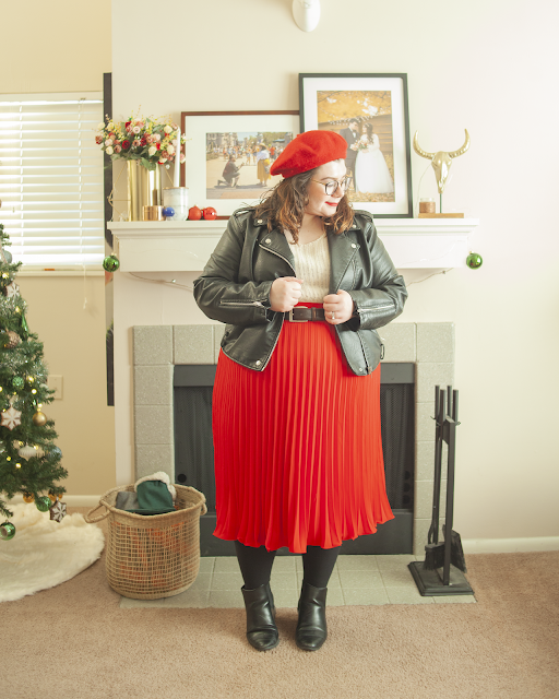 An outfit consisting of a red beret, a black faux leather moto jacket, white sweater tucked into a red pleated tea length skirt and black Chelsea ankle boot