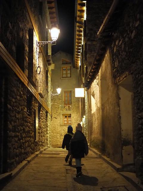 Vista nocturna de un callejón en un pueblo con dos niños andando