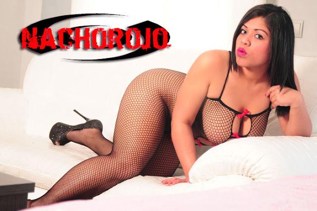 escort latina sobre sofá con conjunto de lencería de red