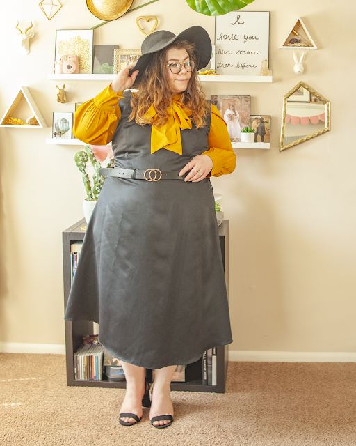 An outfit consisting of a wide brim black floppy hat, a mustard yellow satin blouse with a tie neck collar, tied in a bow, under a black satin sleeveless midi dress and black heels.