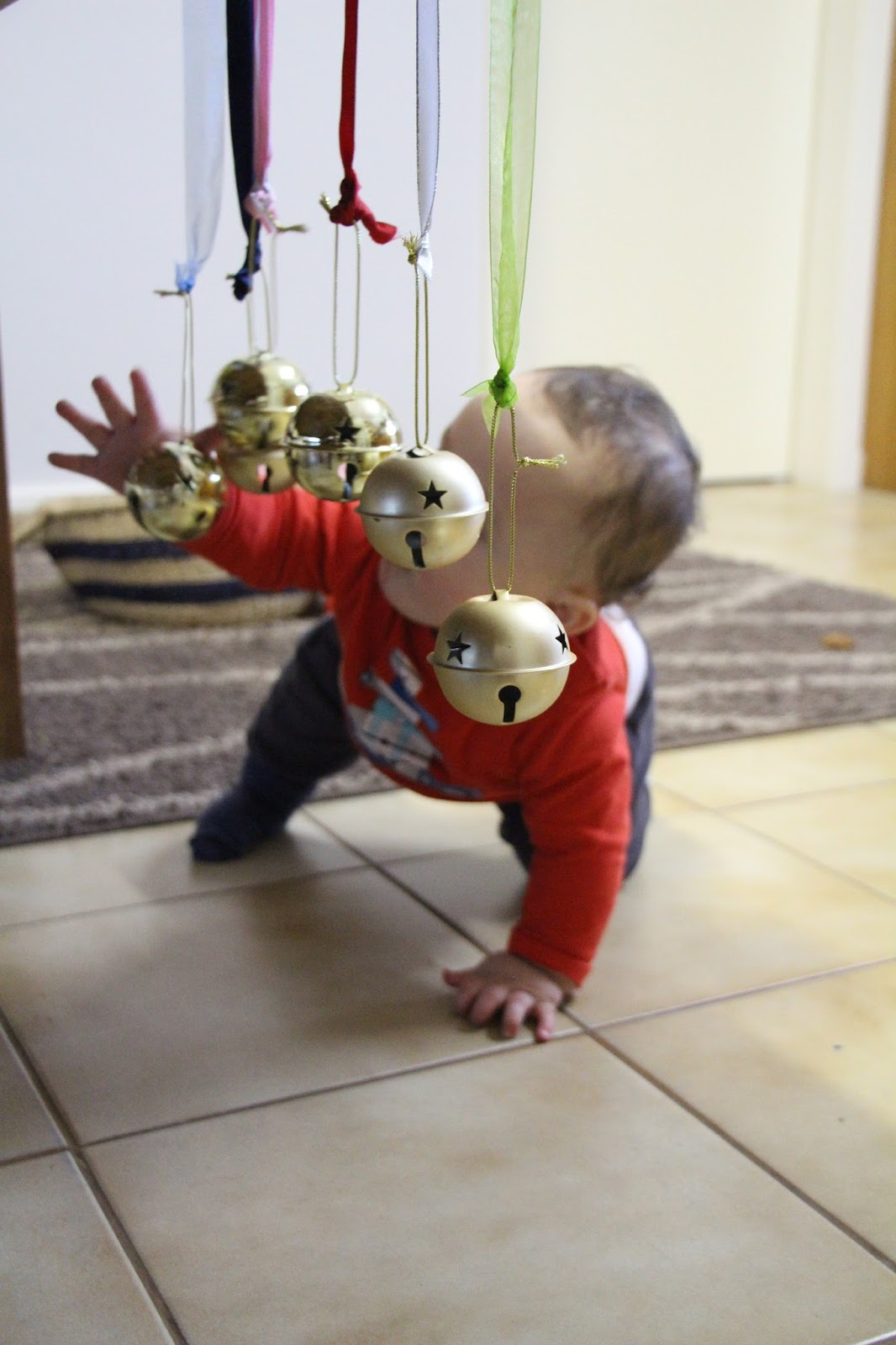 Baby reaching for a bell attached to a mobile