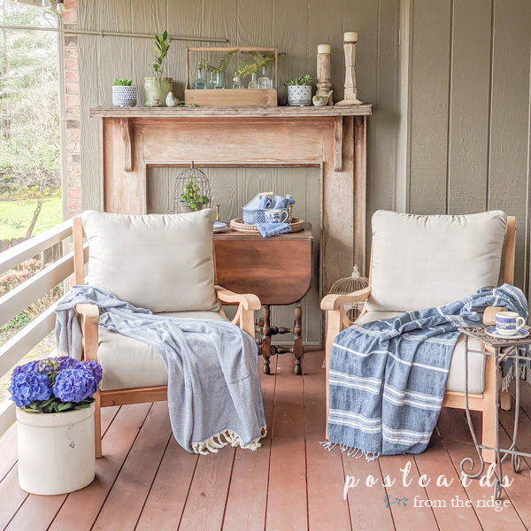teak outdoor chairs with throw blankets and blue and white decor