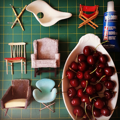 Selection of broken one-tweltfh scale modern chairs laid out next to a bowl of cherries and a tube of glue.