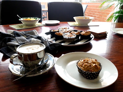 Plate of muffins on an office table, with bowls of lunch in the background.