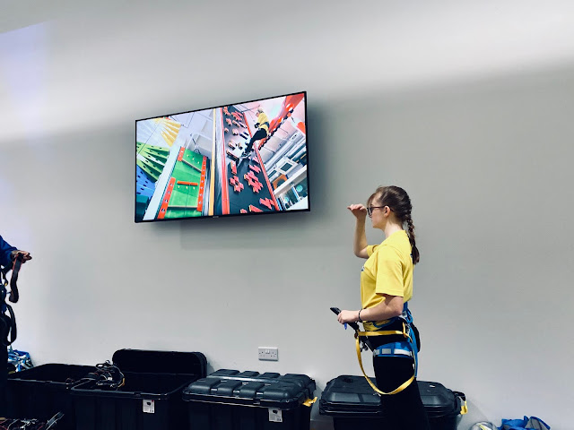 A TV screen with a video on and a member of staff in yellow top next to it