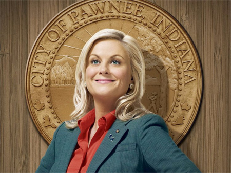 image of Amy Poehler as Leslie Knope from Parks and Recreation, posing in front of a seal for the fictional city of Pawnee, Indiana