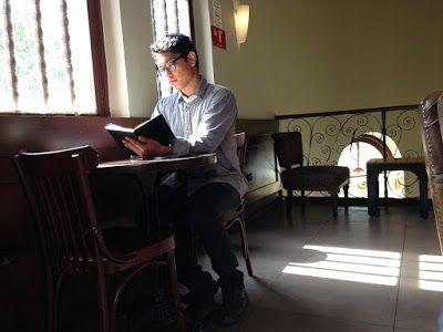 Estudiar correctamente. Joven estudiando en un lugar público,leyendo en la mesa de un bar junto a la ventana