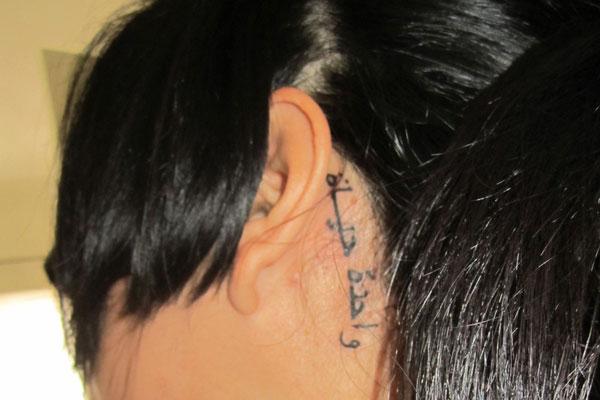 chica con tatuaje arabe detrás de la oreja que dice una vida