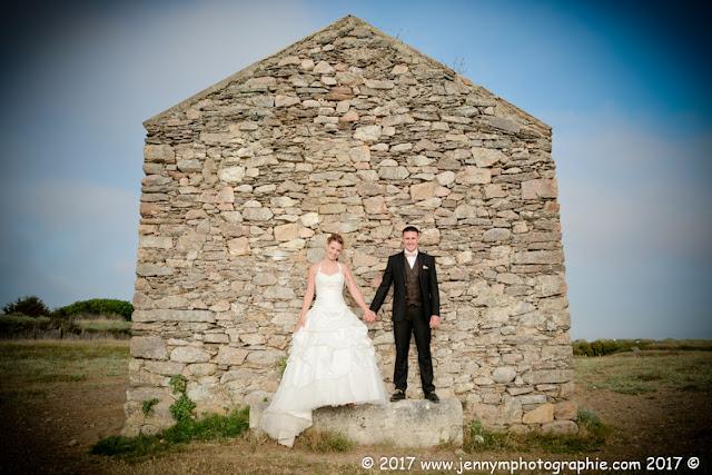 photo mariés qui se tiennent la main devant maison en pierre