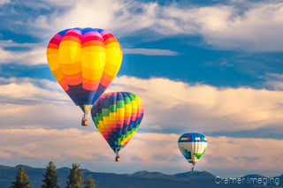 Cramer Imaging's fine art photograph of three hot air balloons taking flight in Panguitch Utah over a trees and mountains