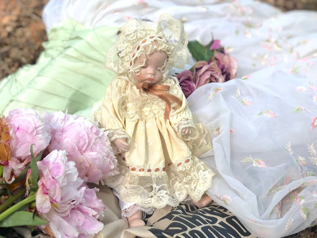 porcelain doll and vintage dress with peonies