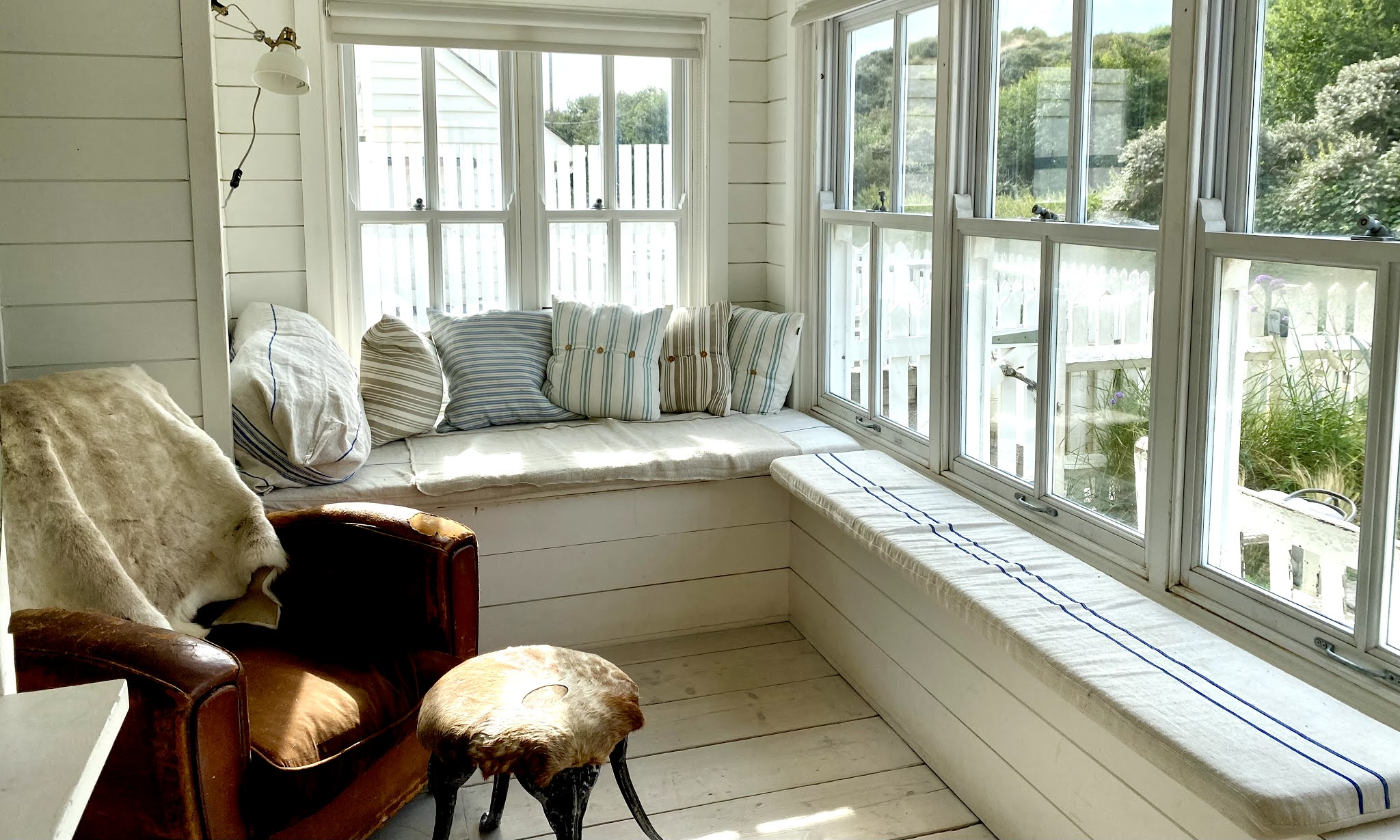 A front room with lots of windows cushions and white