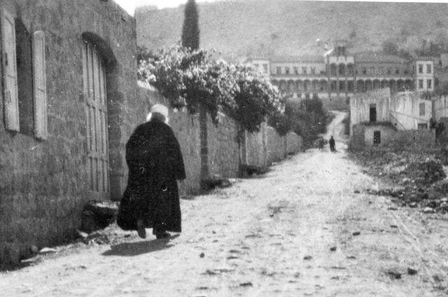 Фотография Абдул-Баха, идущего от Своего дома на улице Хапарсим в Хайфе в 1920 году, — в том же году, когда Первая Скрижаль в Гаагу была доставлена в Центральную организацию за прочный мир.