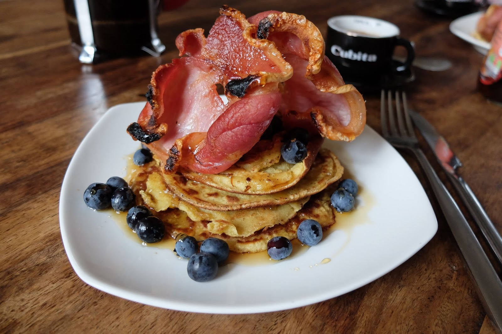 pancake stack with blueberries, bacon and maple syrup
