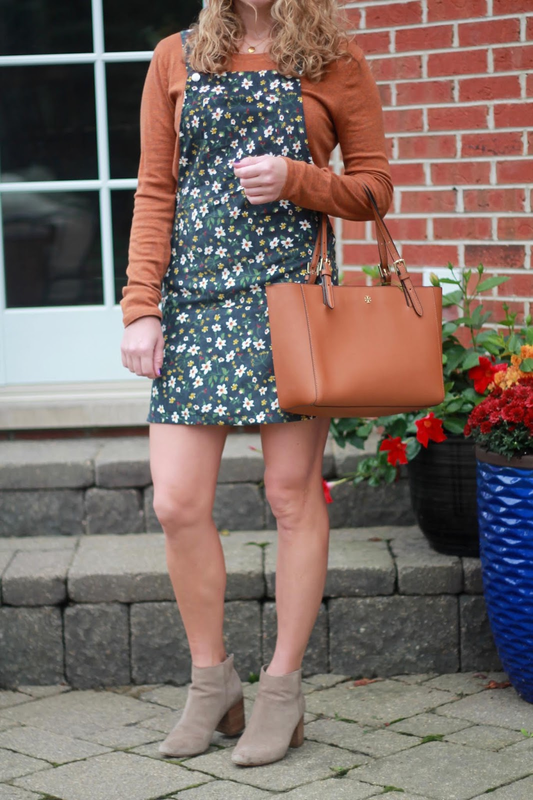rust long sleeve tee, blue floral overall dress, taupe booties, Tory Burch cognac tote