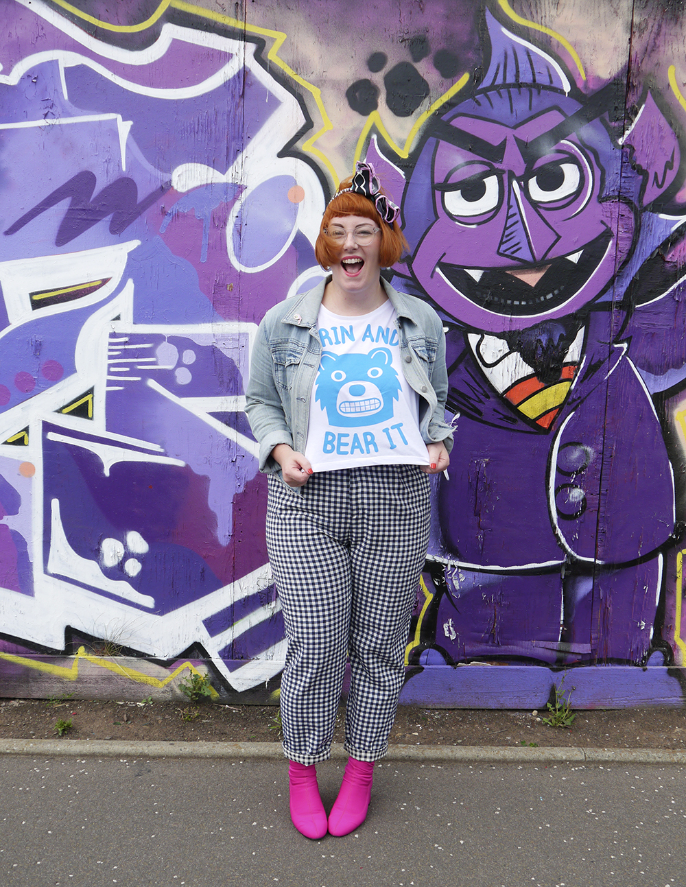 "Scottish bloger wears a hello DODO tshirt featuring a bear with he words ""grin and bear it"" with checked trousers, pink boots and a denim jacket"