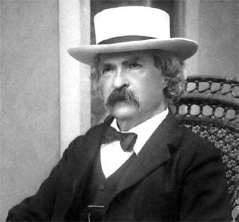 Photograph of Mark Twain seated wearing a white hat, three-piece suit, and a bow tie.