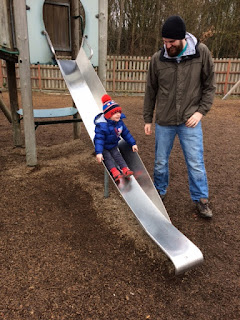 Little boy on a slide being watched by his Daddy