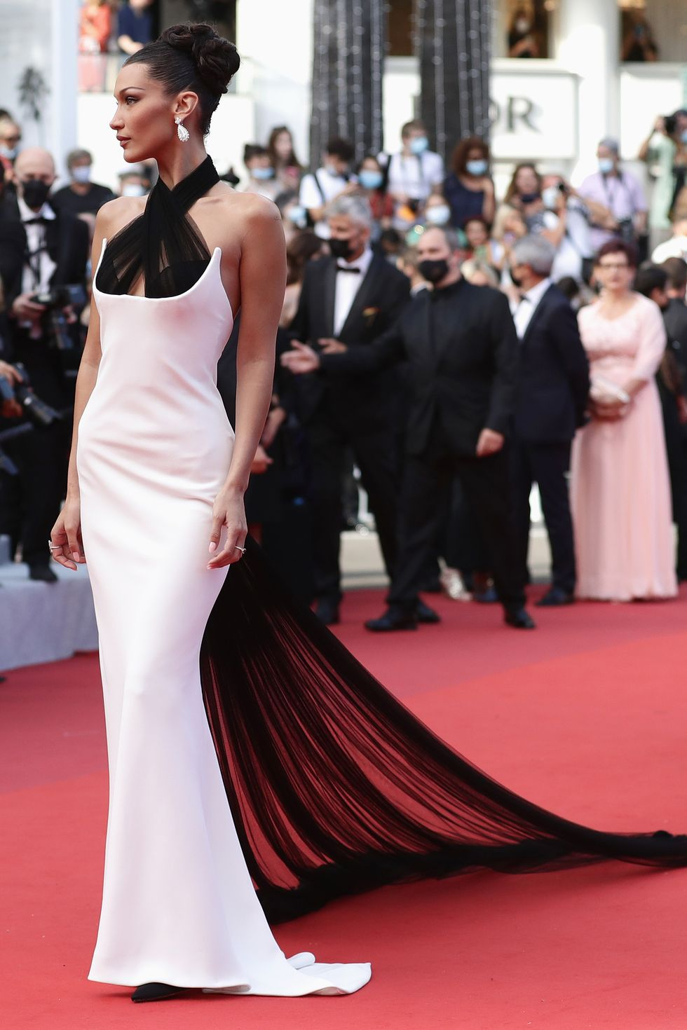 Bella Hadid Bella Hadid made a statement in her classic high-neck Jane Paul gown, which included a long sheer train, and the model completed her look on the red carpet with Chopard jewels.