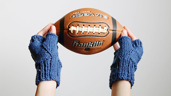 A child's hands wearing hand knit blue fingerless mitts and holding an American football on a white background.