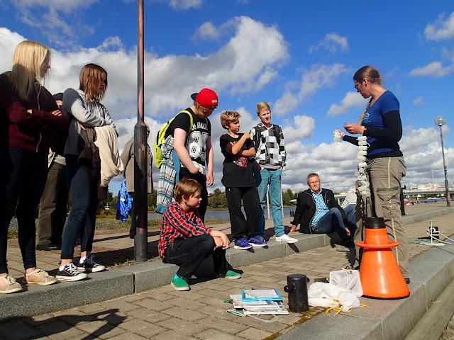 Henkilö esittelee nuorisolle kuvaa, maassa meribiologin varusteita
