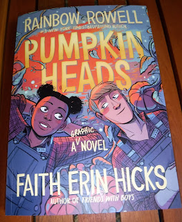 The cover of PumpkinHeads by Rainbow Rowel shows a black girl and a blonde boy wearing matching denim overalls and plaid shirts, and laying on their backs in a pumpkin patch as if gazing at stars