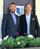 Halvbild på Magnus och Marcus Lidén i skjorta och kavaj ståendes framför en blomsterlåda
