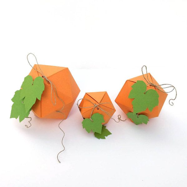 three folded 3D paper pumpkins with leaves and hemp twine