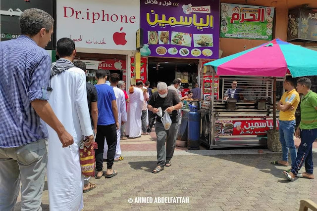 Egyptian men follow social distancing as they get falafel from a small shop