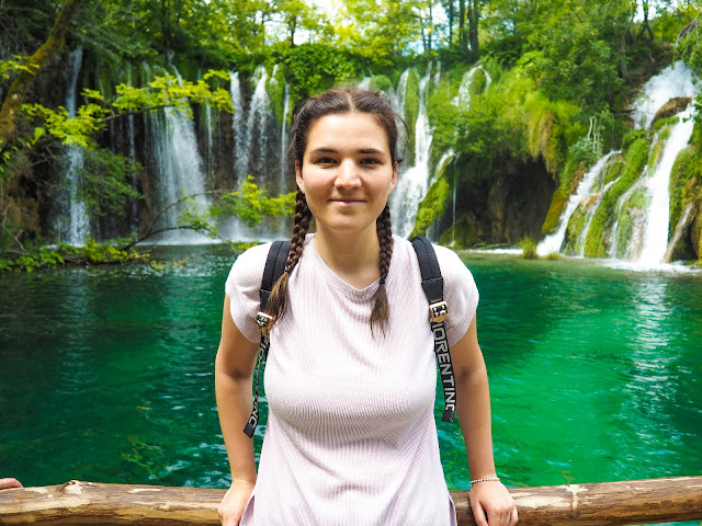 Myself in a pink t shirt in front of waterfalls in Croatia
