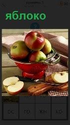 на столе в вазе находятся яблоки и лежат разрезанные половинки
