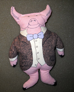 A photograph of a beanbag shaped as a pig in a suit jacket.