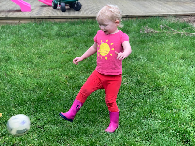 3 year old playing in the garden kicking a ball