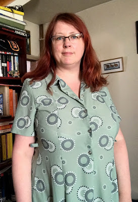 A redheaded woman in a pale green dress with a navy and white print.