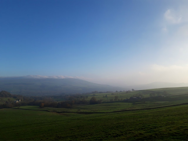 A view over a green Peak District valley.  The sky is blue and there are clouds that look like snow on the hills in the distance