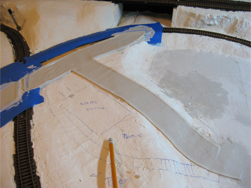 First layer of Woodland Scenics Smooth-It road plaster being applied to forms made from double sided foam tape