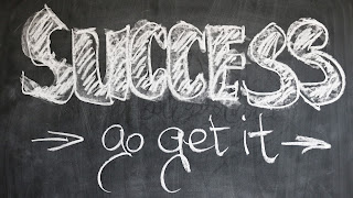 The phrase Success go get it is written in white chalk on a black chalkboard
